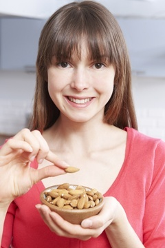 young-woman-eating-almonds-handful almonds badam