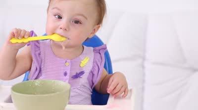 cute-girl-eats-arrowroot -porridge-on-plate-Natureloc baby health mix
