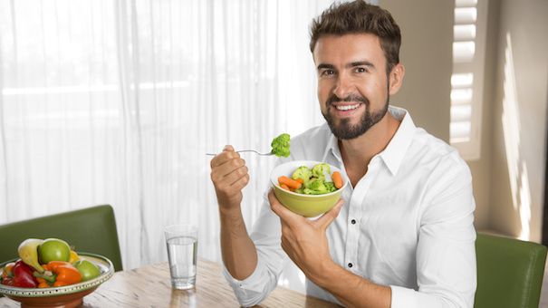 Person drinking water and eating vegetables